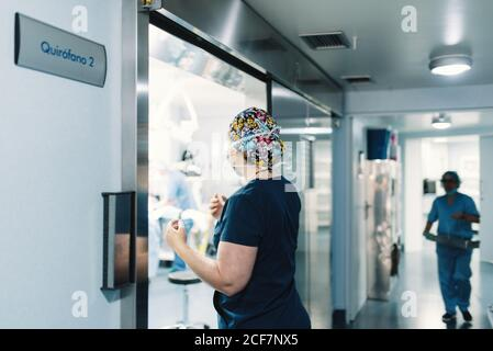 Side view of woman in blue uniform and protective mask coming in operating room and nurse walking along corridor