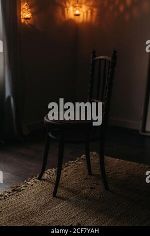 Old wooden chair on floor with carpet in cozy room with lamps - Stock Photo