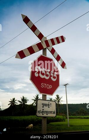 Red road sign saying stop in different languages on highway crossing against cloudy sky, Cambodia - Stock Photo