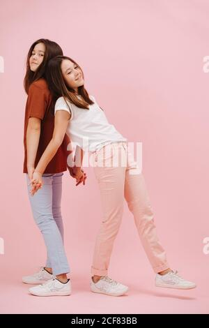 Pretty little twin sisters happily leaning on each other while standing