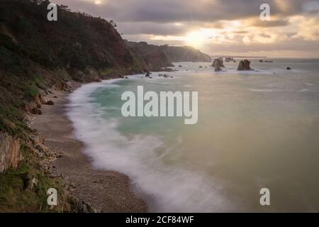 From above scenic peaceful seashore with calm azure waves in light of setting sun on rocky beach of Silence O Gaviero - Stock Photo