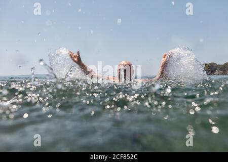 Bald mustache elderly man enjoying and splashing water in bright sunny day in Greece Halkidiki