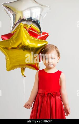 Little baby girl holding balloons in the form of stars. Young girl holding a star shaped balloons. Happy child with colorful shiny foil balloons again - Stock Photo