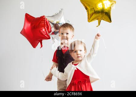 Little kids holding balloons in the form of stars. Children holding a star-shaped balloons. Happy children with colorful shiny foil balloons against a - Stock Photo