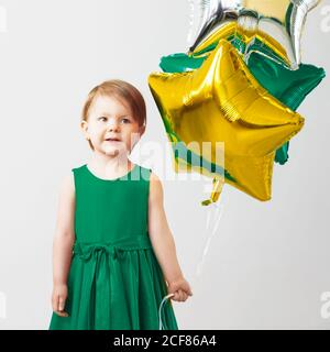 Little baby girl holding balloons in the form of stars. Young girl holding a star-shaped balloons. Happy child with colorful shiny foil balloons again - Stock Photo