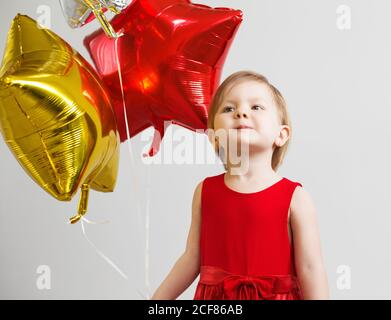 Little baby girl holding balloons in the form of stars. Young girl holding a star-shaped balloons. Happy child with colorful shiny foil balloons - Stock Photo