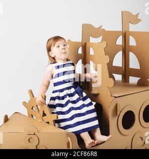Cute  Little girl wearing striped dress in a marine style playing with cardboard ship on white background. Happy children. Childhood. Fantasy, imagina - Stock Photo