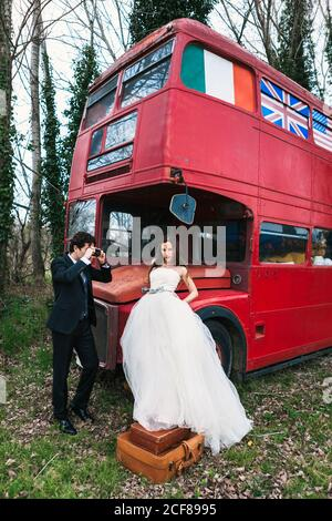 Elegant groom in suit taking photo of bride in white wedding dress standing on vintage suitcases near double decker bus Stock Photo