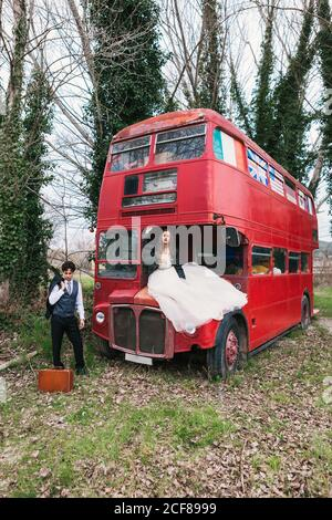Bride in wedding dress sitting on hood of old double decker bus and groom in classy tuxedo standing near suitcase in wood Stock Photo