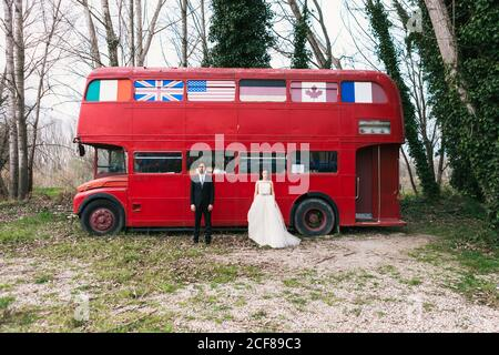 Bride in elegant wedding dress and groom in classy suit standing near vintage red bus during wedding day and looking at camera Stock Photo