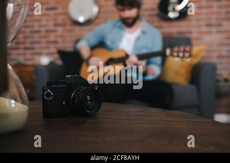Crop bearded guy in denim jacket playing acoustic guitar while sitting on cozy couch in front of wooden table with photo camera and hourglass at home