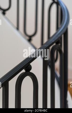 Solid wooden staircase with black railing in house with light interior - Stock Photo