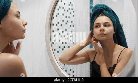 Young woman has problems with skin on the face - She looks in the mirror in the bathroom