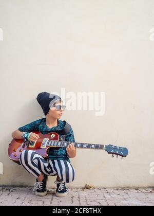 Cheeky active excited boy in colorful clothes playing guitar sitting leaning on background of white wall - Stock Photo