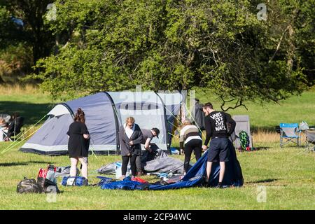 Group of friends taking down their tent at We Are Not a Festival socially distanced event in Pippingford Park - camping with a festival vibe - Stock Photo