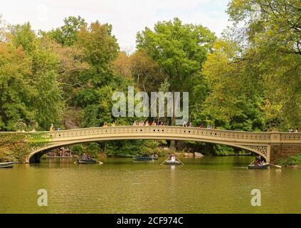 New York City, USA - October 7, 2019: The Bow Bridge in Central Park. Pepole walking across the bridge or looking in the lake. Rowing boats are under