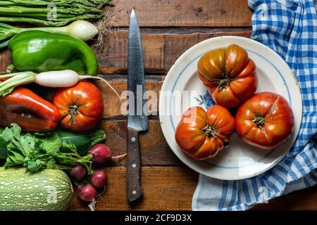 Fresh organic vegetables on a dark wooden table with tomatoes in a bowl and a knife - Stock Photo