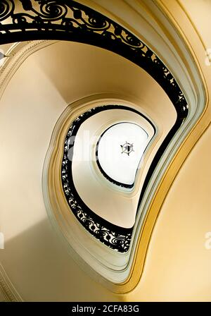 From below white elegant spiral stairway with black ornamental banister located inside classic building - Stock Photo