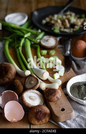 From above ripe scallions and mushrooms placed near eggshells and poppy seeds on table in rustic kitchen - Stock Photo