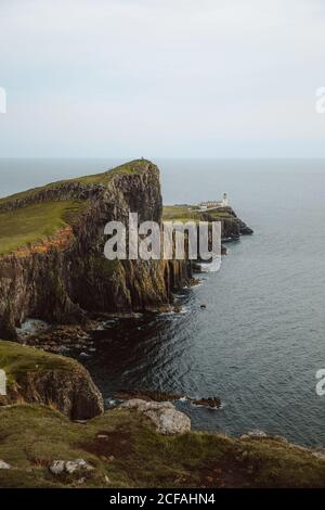 From above majestic view of Neist Point Lighthouse built on high rocks surrounded by dark water on daytime - Stock Photo