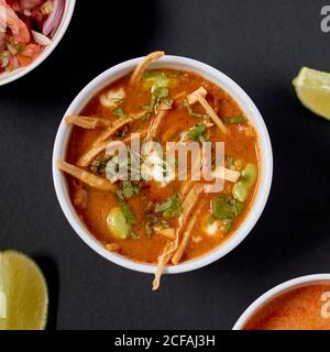 From above yummy nutrient tomato soup with sour cream and aromatic green herbs in white ceramic bowl on gray table beside variety other dishes - Stock Photo