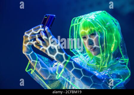 Young Asian woman in futuristic wear and green wig taking selfie on smartphone in fluorescent light
