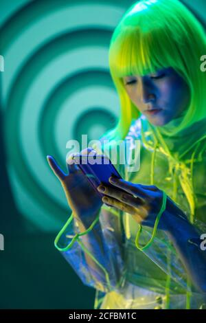 Young asian woman in futuristic wear and green wig using smartphone in fluorescent light