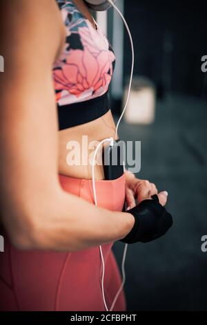 Side view of crop female boxer in sportswear with bandage on wrist listening to music with smartphone and headphones while resting after training in gym