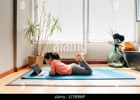 Side view of positive little girl lying down on mat near window at home resting after practicing yoga throughout video tutorials on tablet