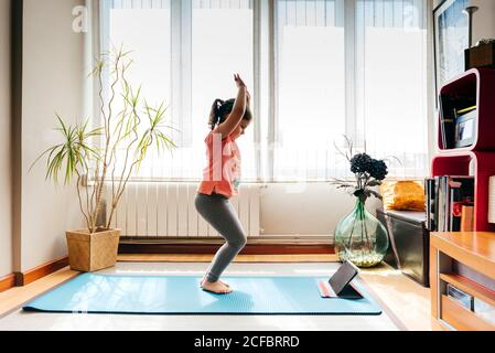 Side view of positive little girl standing in yoga pose on mat near window at home while practicing yoga and watching video tutorials on tablet