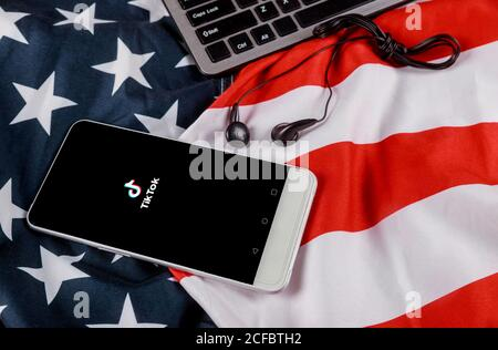 NEW YORK NY September 02 2020: Tik Tok application icon on smartphone screen American flag waving with modern headphones with cellphone - Stock Photo