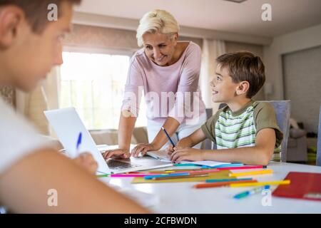 Mother helping her kids doing homework at home