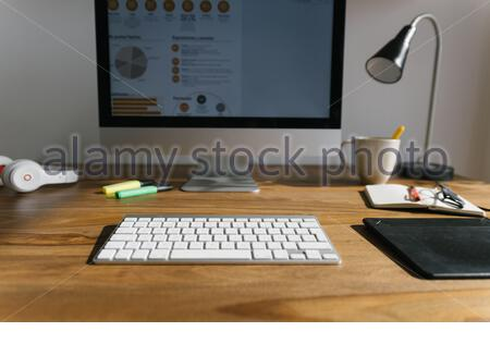Interior of modern workspace with personal computer tablet and headphones on wooden desktop above table locating near big glass wall in light trendy living room at home - Stock Photo