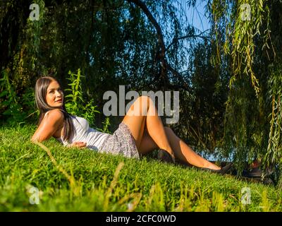 Young woman beautiful 20-25yo 20-25 yo acting countrygirl countryside meadow park forest woodland trees near river lake riverside slope slight smile - Stock Photo
