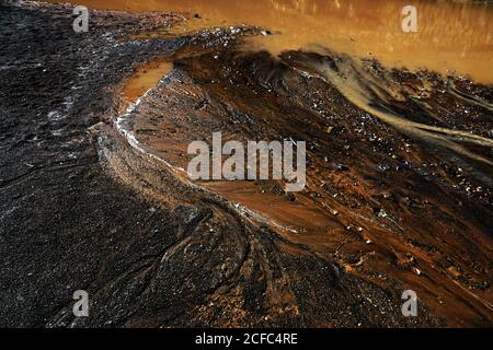 From above abstract dark ground with dirty puddle and dripping rusty water flows - Stock Photo