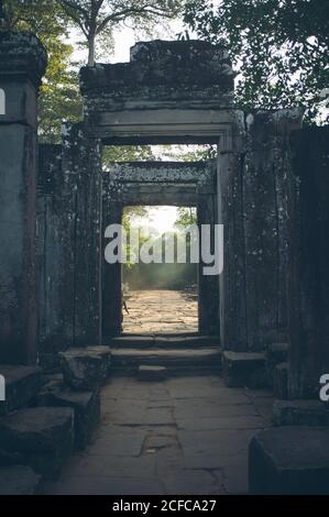 Perspective view through stone gates of green garden on territory of ancient temple in Thailand