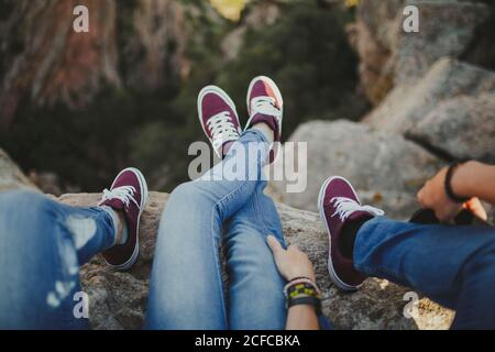 Crop from above feet relaxed couple in matching denim outfit and sneakers lying in embrace on cliff enjoying view
