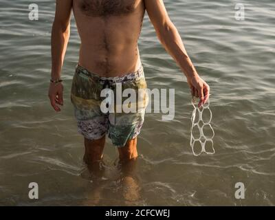From above anonymous male with hairy chest carrying plastic waste while standing in sea water on resort