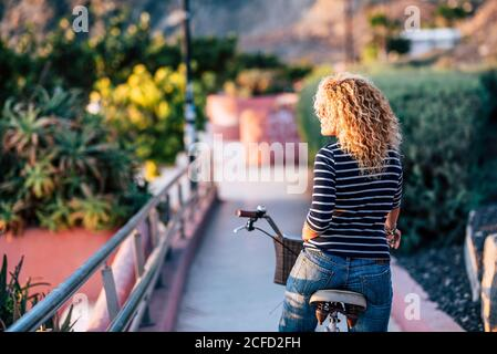 Beautiful blonde curly hair woman viewed from back - people in healthy bike ride activity in the city park - free from stay home concept emergency Stock Photo