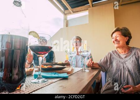 Group of senior people enjoy elderly lifestyle together having fun with food and beverages - home and restaurant celebrate activity for old happy - Stock Photo
