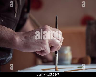 Closeup hand of anonymous artist using paintbrush and green paint to draw picture on canvas in studio