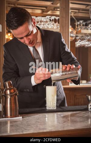 Mixologist pouring white liquid into glass while preparing cocktail behind counter in bar of luxury hotel - Stock Photo