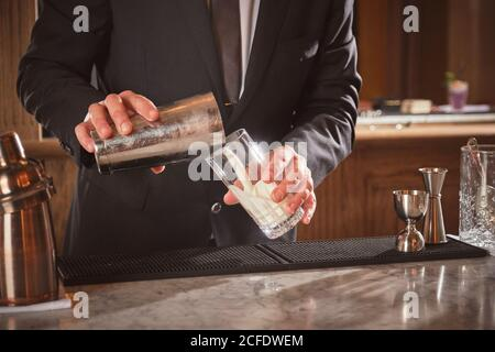 anonymous mixologist pouring white liquid into glass while preparing cocktail behind counter in bar of luxury hotel - Stock Photo