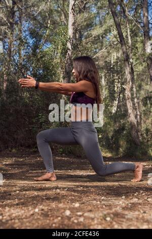 Full body of young fit woman in sportswear practicing variation of Anjaneyasana during yoga class in spring forest on fresh air