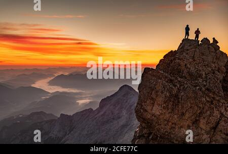 Three young men on top of the Zugspitze, Germany's highest mountain, at sunrise in autumn, with a view over the Alpspitze towards the Isar Valley,