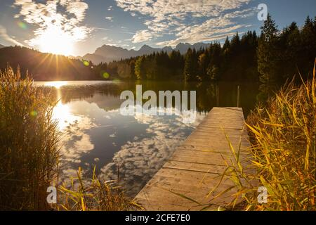 View from Badesteg near Geroldsee towards the Karwendel mountains at sunrise, blue sky, water reflection, sun rays, trees, reeds, clouds, Krün, - Stock Photo