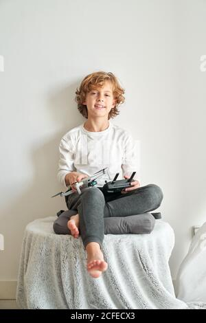 Child manipulating a drone and the remote control just given to him