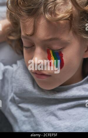 From above cute boy in pajama and with rainbow under eye lying on pillow and blanket and sleeping while staying home during quarantine Stock Photo
