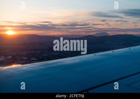 View from window of wing of modern aircraft flying over dense clouds during sunset time