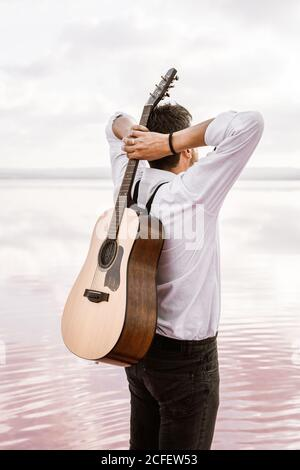From behind man in white shirt holding acoustic guitar behind back while standing on shore on cloudy day in USA